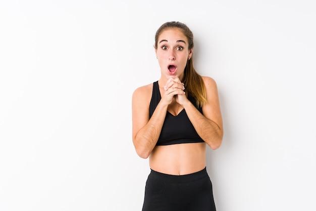 Giovane donna indoeuropea fitness in posa in un muro bianco pregando per fortuna, stupito e aprendo la bocca guardando in avanti.