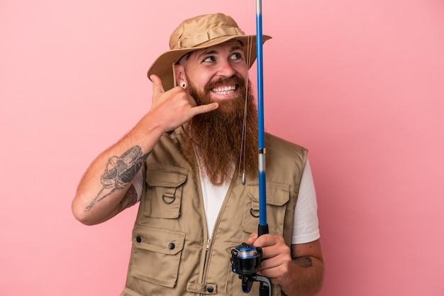 Giovane pescatore caucasico dello zenzero con la barba lunga che tiene un'asta isolata su fondo rosa che mostra un gesto di chiamata del telefono cellulare con le dita.
