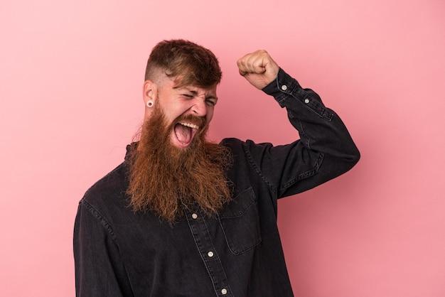 Giovane uomo caucasico di zenzero con barba lunga isolato su sfondo rosa che celebra una vittoria, passione ed entusiasmo, espressione felice.