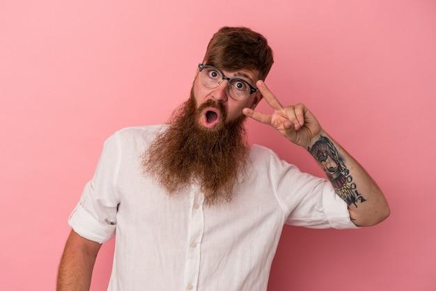 Giovane uomo caucasico zenzero con barba lunga isolato su sfondo rosa ballare e divertirsi.