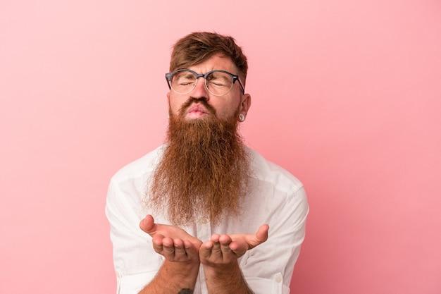Giovane uomo caucasico di zenzero con barba lunga isolato su sfondo rosa piegando le labbra e tenendo i palmi delle mani per inviare un bacio d'aria.