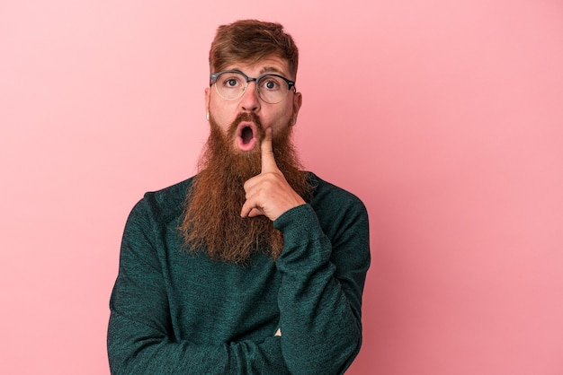 Giovane uomo caucasico di zenzero con barba lunga isolato su sfondo rosa con qualche grande idea, concetto di creatività.
