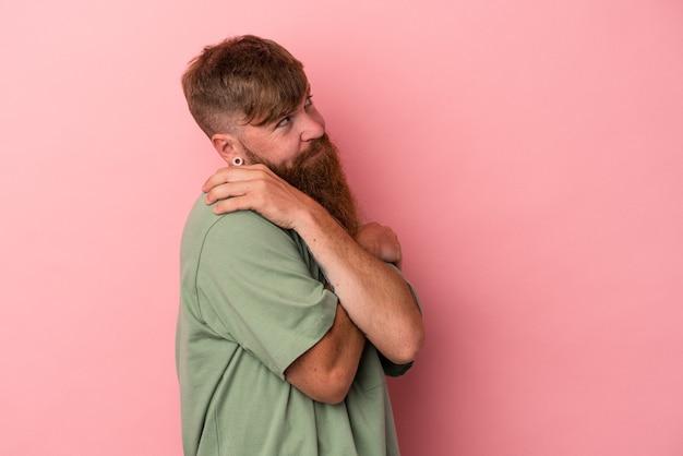 Il giovane uomo caucasico dello zenzero con la barba lunga isolato sugli abbracci rosa del fondo, sorride spensierato e felice.