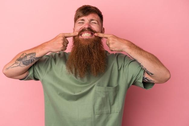 Il giovane uomo caucasico dello zenzero con la barba lunga isolata sui sorrisi rosa del fondo, indicando le dita alla bocca.