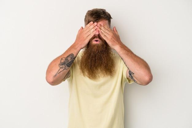 Giovane uomo caucasico dello zenzero con la barba lunga isolata su fondo bianco impaurito che copre gli occhi con le mani.