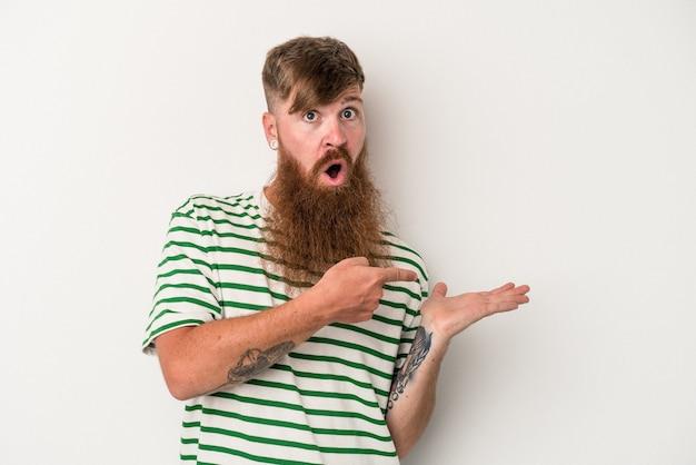 Il giovane uomo caucasico dello zenzero con la barba lunga isolato su fondo bianco ha eccitato tenendo uno spazio della copia sul palmo.