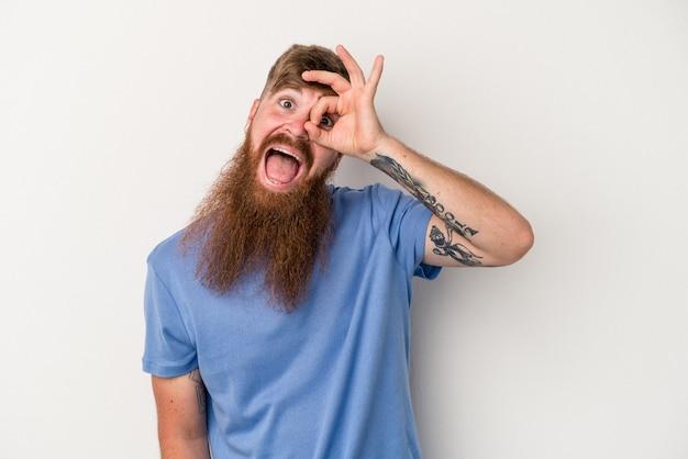 Il giovane uomo caucasico dello zenzero con la barba lunga isolato su fondo bianco ha eccitato mantenendo il gesto giusto sull'occhio.