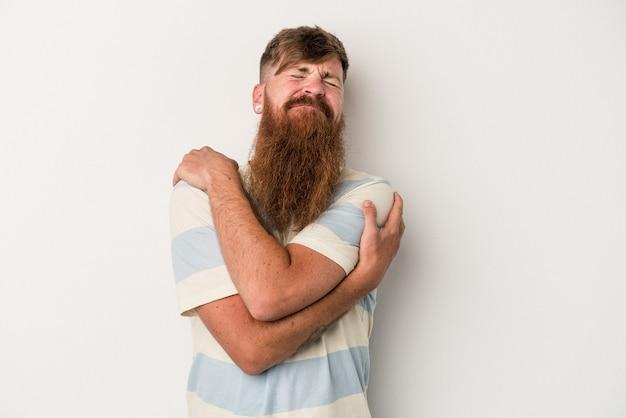 Il giovane uomo caucasico dello zenzero con la barba lunga isolato sugli abbracci bianchi del fondo, sorride spensierato e felice.