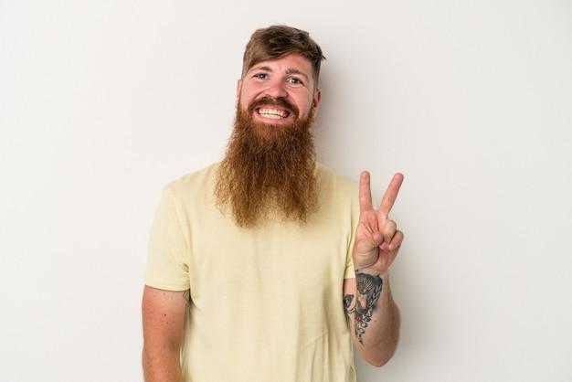 Giovane uomo caucasico dello zenzero con la barba lunga isolato su fondo bianco gioioso e spensierato che mostra un simbolo di pace con le dita.