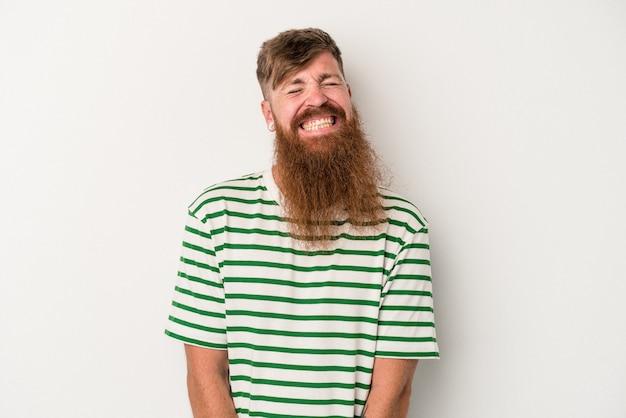Il giovane uomo caucasico dello zenzero con la barba lunga isolato su fondo bianco ride e chiude gli occhi, si sente rilassato e felice.