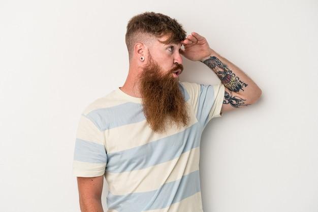 Giovane uomo caucasico dello zenzero con la barba lunga isolata su fondo bianco che guarda lontano tenendo la mano sulla fronte.
