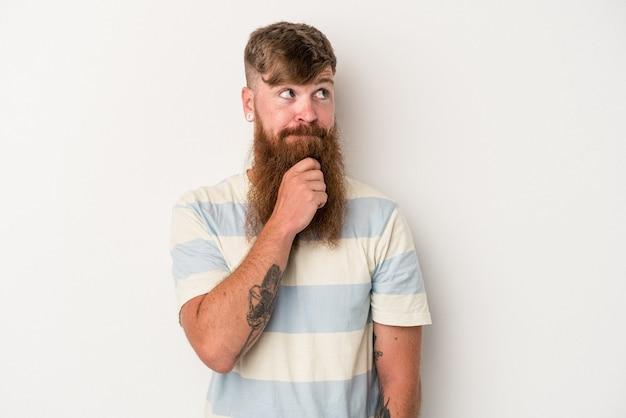 Giovane uomo caucasico zenzero con barba lunga isolato su sfondo bianco guardando lateralmente con espressione dubbiosa e scettica.