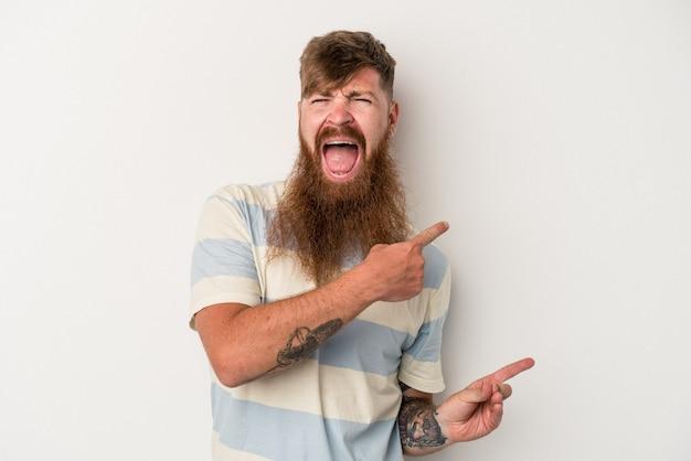 Giovane uomo caucasico di zenzero con barba lunga isolato su sfondo bianco che punta con l'indice a uno spazio di copia, esprimendo eccitazione e desiderio.
