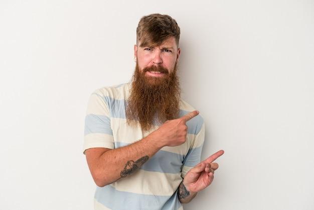 Il giovane uomo caucasico dello zenzero con la barba lunga isolato su fondo bianco ha colpito che indica con le dita indice uno spazio della copia.