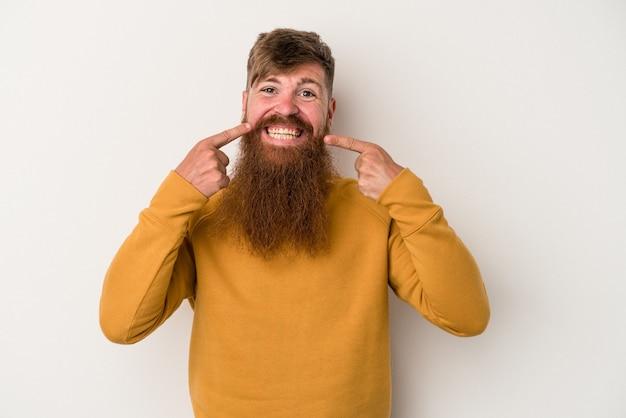 Il giovane uomo caucasico dello zenzero con la barba lunga isolato sui sorrisi bianchi del fondo, indicando le dita alla bocca.