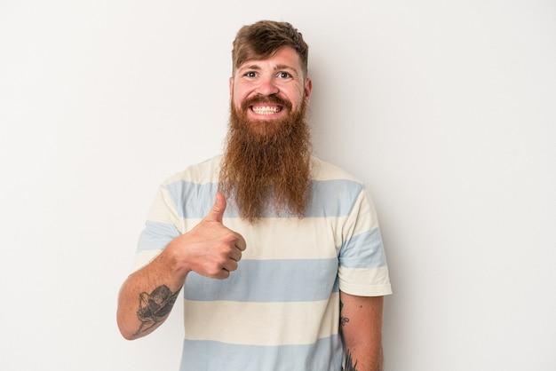 Giovane uomo caucasico dello zenzero con la barba lunga isolato su fondo bianco che sorride e che alza pollice su