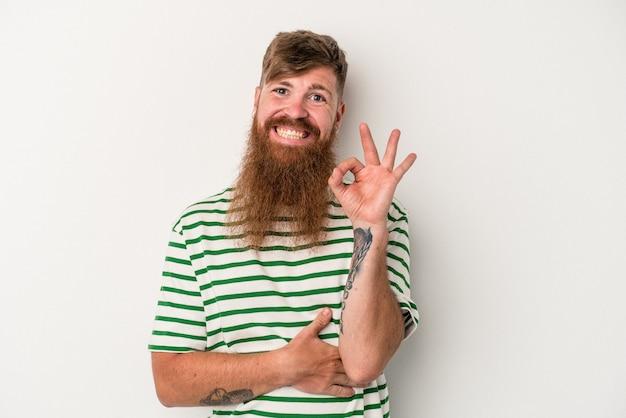 Il giovane uomo caucasico dello zenzero con la barba lunga isolata su fondo bianco strizza l'occhio e tiene un gesto giusto con la mano.