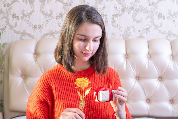 Giovane ragazza caucasica che tiene in mano una confezione regalo bianca con un nastro rosso e una rosa d'oro a casa, vista frontale, spazio copia. san valentino, festa della mamma, compleanno, concetto di fidanzamento