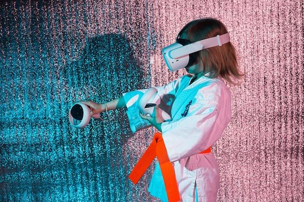 Giovane ragazza caucasica in uniforme di karate che gioca ai videogiochi con la realtà virtuale