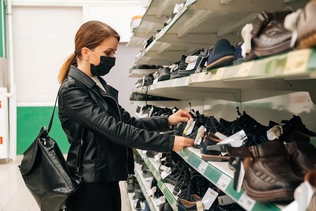 Una giovane ragazza caucasica in una maschera medica nera sceglie vestiti, prodotti di scarpe al supermercato. il concetto di distanza sociale e