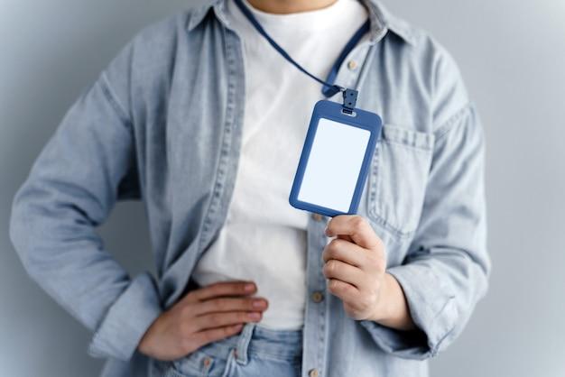 Giovane ragazza caucasica che mostra etichetta nome su sfondo grigio
