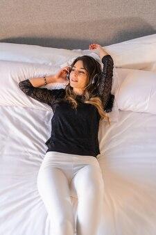 Giovane ragazza caucasica con pantaloni neri e bianchi e con le cuffie che ascoltano musica rilassata