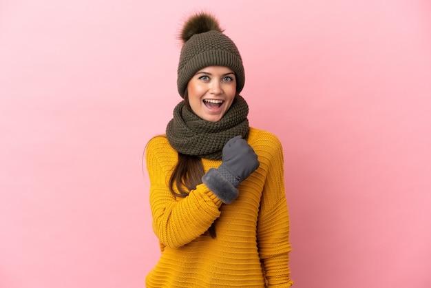 Giovane ragazza caucasica con cappello invernale isolato su sfondo rosa che celebra una vittoria