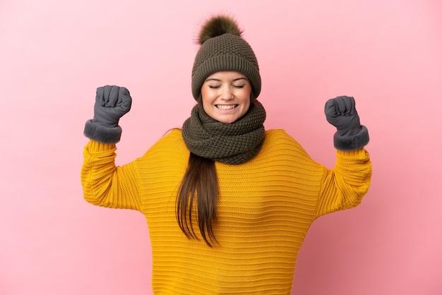 Giovane ragazza caucasica con cappello invernale isolato su sfondo rosa che fa un gesto forte