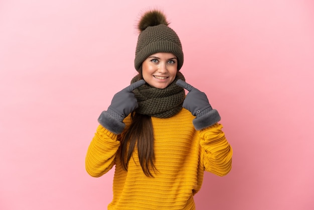 Giovane ragazza caucasica con cappello invernale isolato su sfondo rosa che dà un gesto di pollice in alto