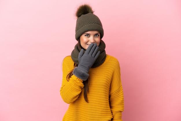 Giovane ragazza caucasica con cappello invernale isolato su sfondo rosa felice e sorridente che copre la bocca con la mano
