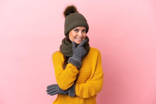 Giovane ragazza caucasica con cappello invernale isolato su sfondo rosa felice e sorridente