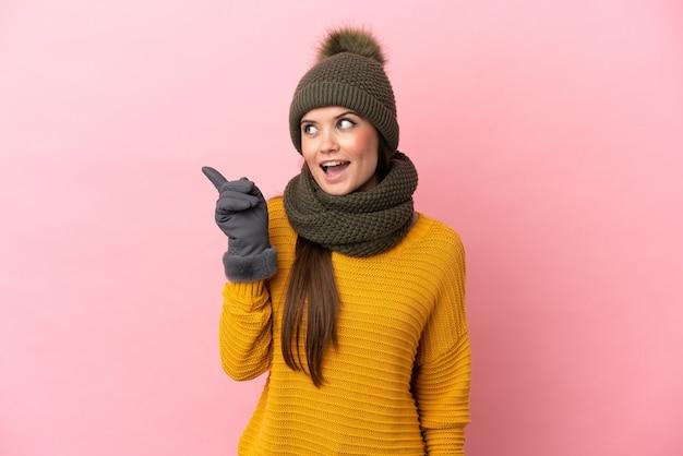Giovane ragazza caucasica con cappello invernale isolato su sfondo rosa con l'intenzione di realizzare la soluzione mentre si solleva un dito