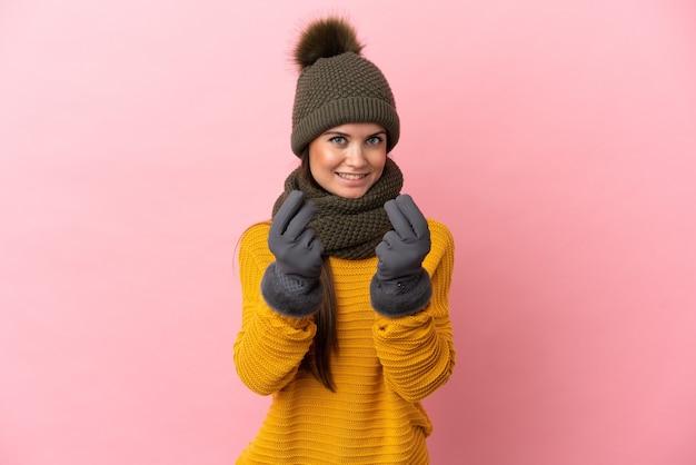 Giovane ragazza caucasica con cappello invernale isolato su sfondo rosa che fa gesto di soldi