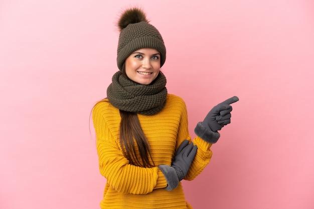 Giovane ragazza caucasica con cappello invernale isolato su sfondo rosa che punta il dito a lato