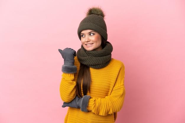 Giovane ragazza caucasica con cappello invernale isolato su sfondo rosa che punta al lato per presentare un prodotto
