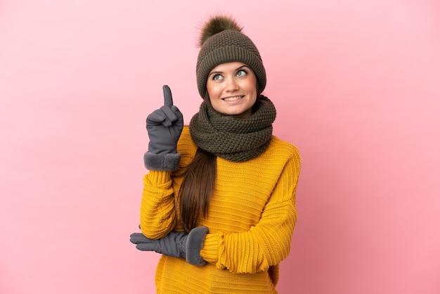 Giovane ragazza caucasica con cappello invernale isolato su sfondo rosa che indica una grande idea