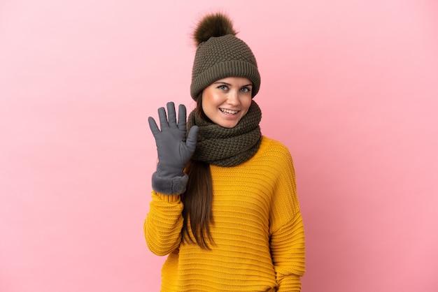 Giovane ragazza caucasica con cappello invernale isolato su sfondo rosa che saluta con la mano con espressione felice