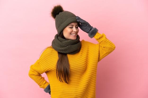Giovane ragazza caucasica con cappello invernale isolato su sfondo rosa che sorride molto
