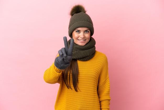 Giovane ragazza caucasica con cappello invernale isolato su sfondo rosa che sorride e mostra il segno della vittoria