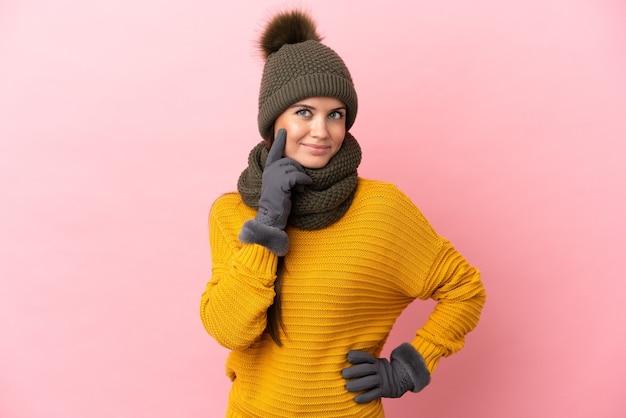 Giovane ragazza caucasica con cappello invernale isolato su sfondo rosa pensando a un'idea mentre guarda in alto