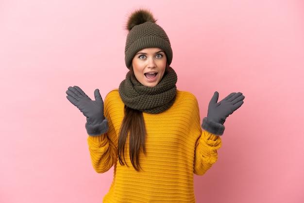 Giovane ragazza caucasica con cappello invernale isolato su sfondo rosa con espressione facciale scioccata