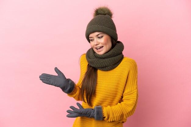 Giovane ragazza caucasica con cappello invernale isolato su sfondo rosa con espressione di sorpresa mentre guarda di lato