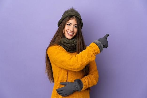 Giovane ragazza caucasica con cappello invernale isolato su sfondo viola rivolto indietro