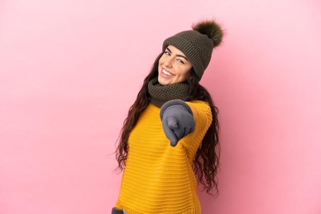 Giovane ragazza caucasica con cappello invernale isolato su sfondo viola che punta davanti con espressione felice