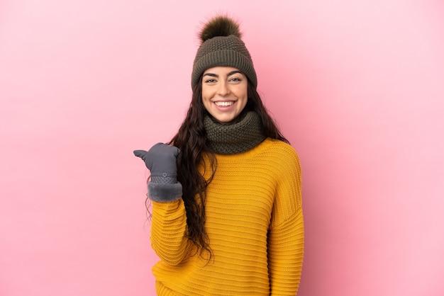 Giovane ragazza caucasica con cappello invernale isolato su sfondo viola che punta al lato per presentare un prodotto