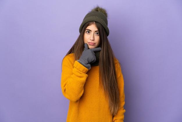 Giovane ragazza caucasica con cappello invernale isolato su sfondo viola pensando