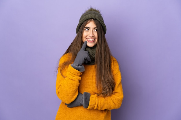 Giovane ragazza caucasica con cappello invernale isolato su superficie viola pensando a un'idea mentre guarda in alto