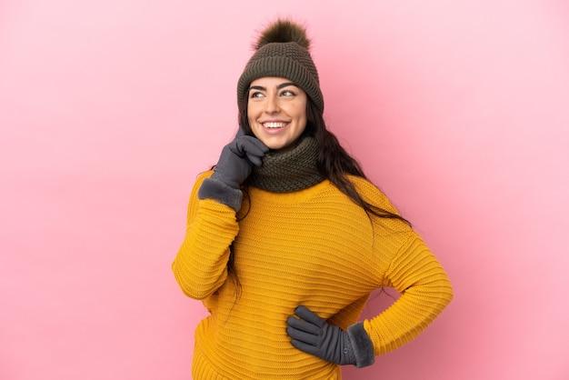 Giovane ragazza caucasica con cappello invernale isolato sulla parete viola pensando un'idea mentre guarda in alto
