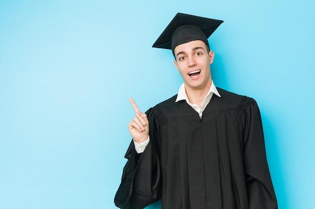 Giovane uomo caucasico laureato che sorride allegramente indicando con l'indice di distanza.