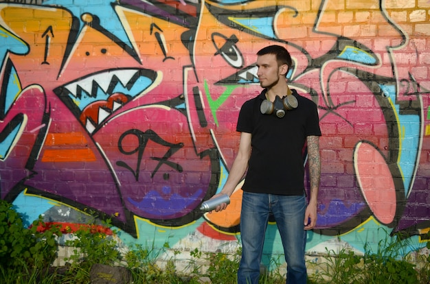 Giovane artista caucasico dei graffiti in maglietta nera con la bomboletta spray d'argento vicino ai graffiti variopinti